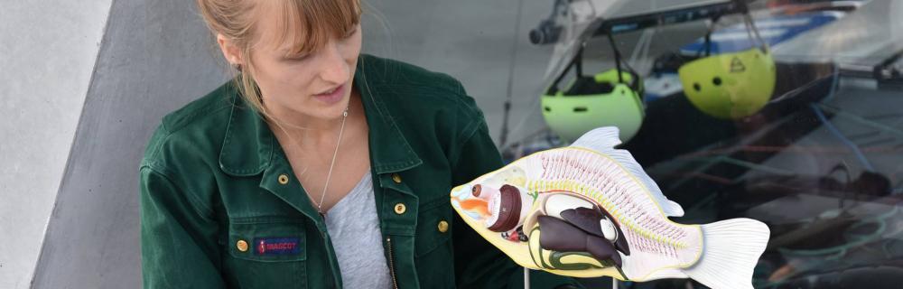 Kvinde viser en model af en fisk